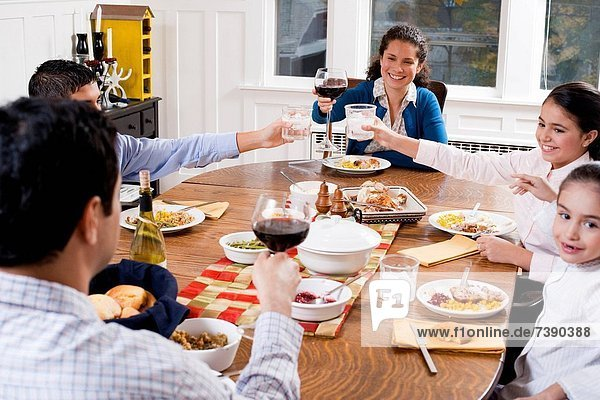 Family at dinner table toasting