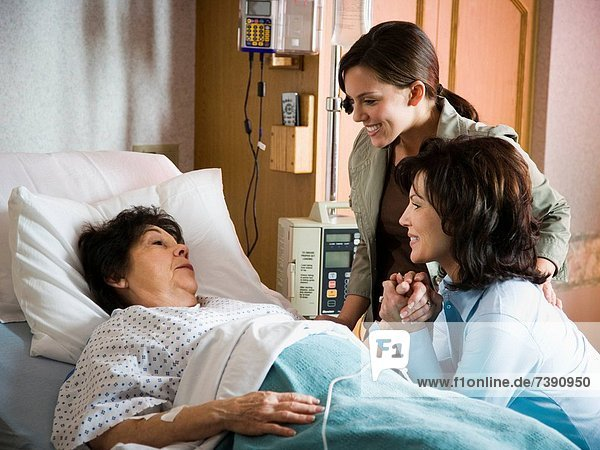 Two women talking with mature woman in hospital