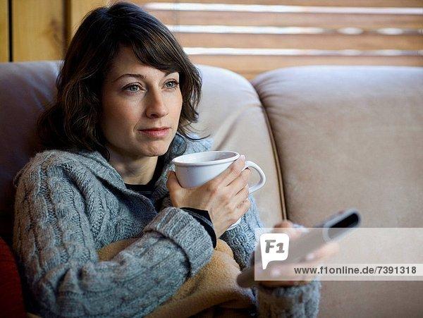 Woman on sofa with coffee mug and remote