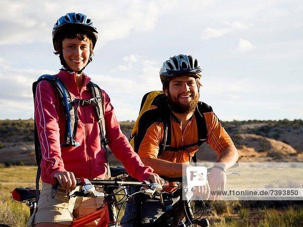 Außenaufnahme  Frau  Mann  Helm  lächeln  Fahrrad  Rad  freie Natur