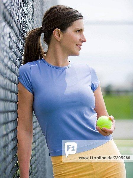 angelehnt  Frau  lächeln  Zaun  Ball Spielzeug  Tennis