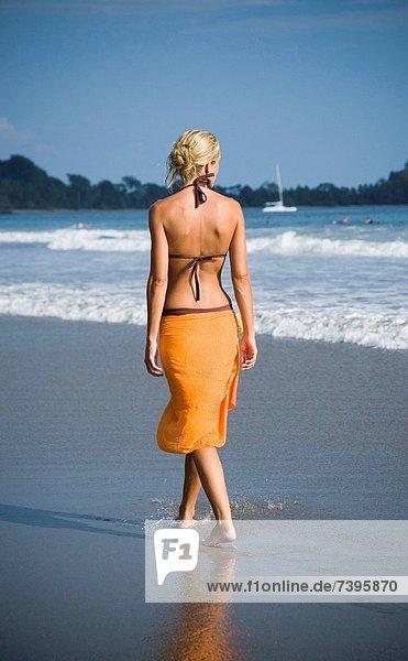 Frau läuft am Strand entlang