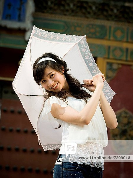 Teenage girl outdoors with umbrella smiling