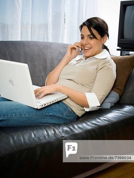 USA  Utah  Orem  woman lying on sofa using laptop and cell phone