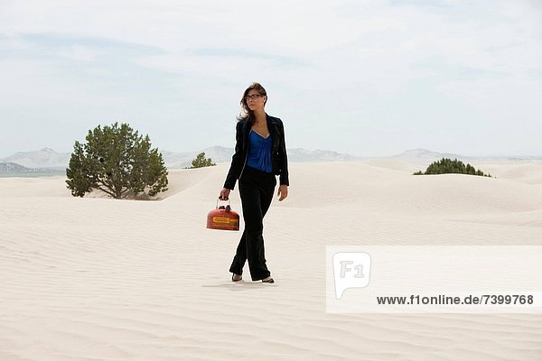 USA  Utah  Little Sahara  young businesswoman walking on desert carrying gas can