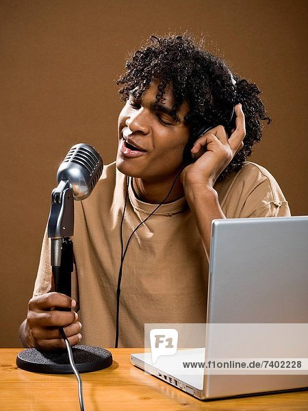 young man in a brown shirt on a laptop with headphones and a microphone.