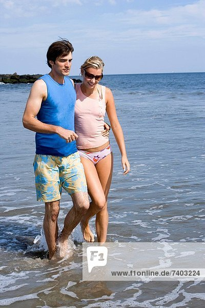 Couple walking on shallow water at the beach