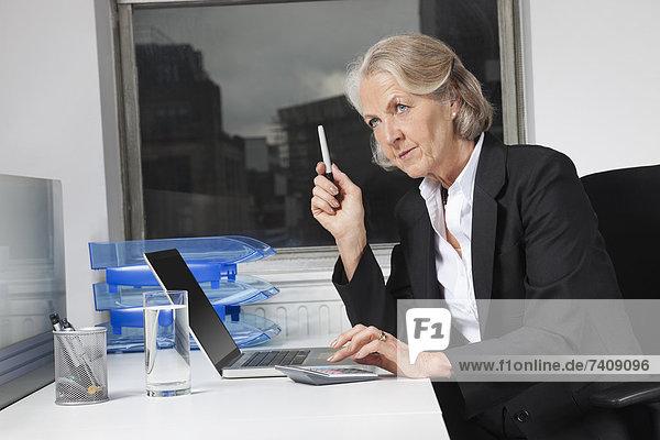 Senior  Senioren  benutzen  Geschäftsfrau  Schreibtisch  Notebook  Taschenrechner  Büro