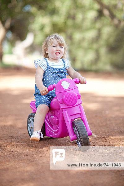 Kleinkind Mädchen Reiten Spielzeug auf Schotterpiste