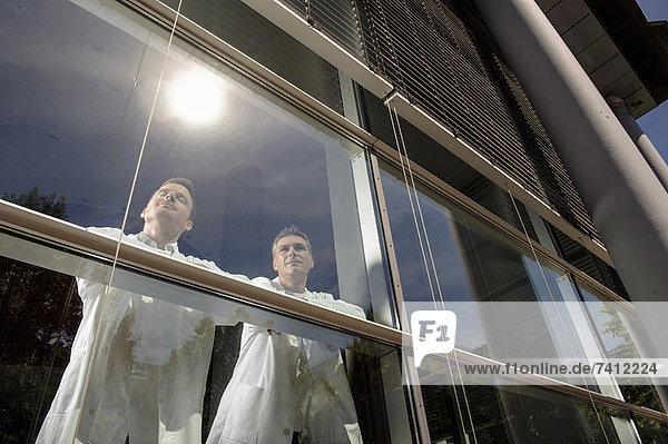 Ärzte stehen am Bürofenster