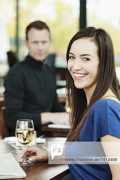 Frau trinkt Wein im Café