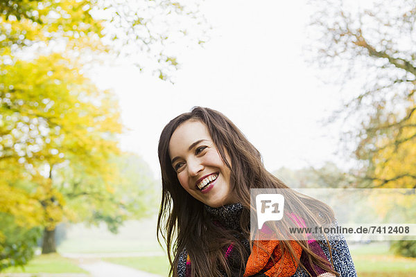 Lächelnde Frau im Wald stehend