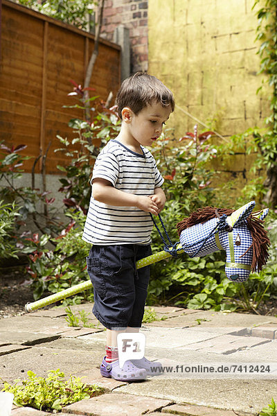 Boy playing with toy horse in garden
