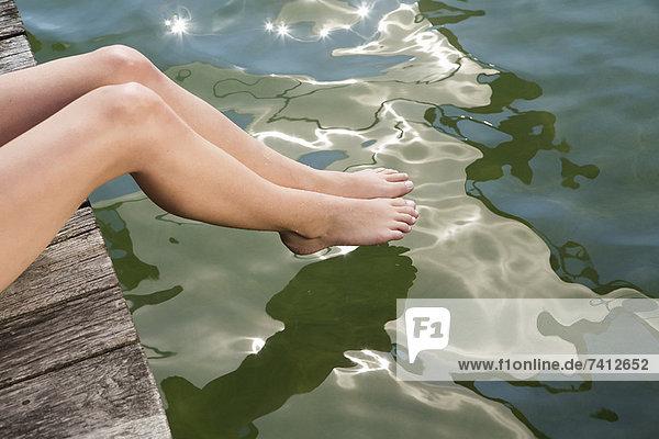 Frau taucht Zehen in den stillen See