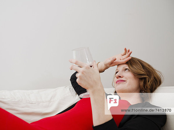 Frau trinkt Wein auf dem Sofa