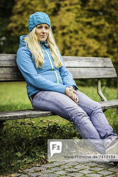 Frau auf Parkbank sitzend