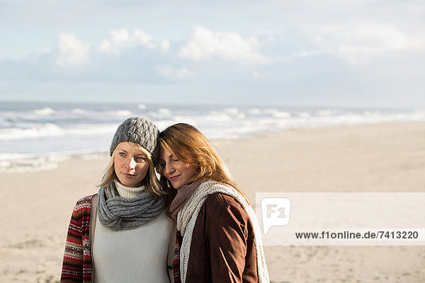 Frauen umarmen sich am Strand