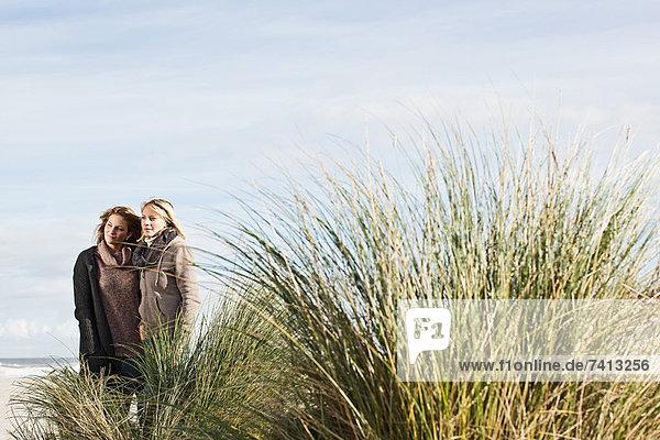 Frau steht zusammen am Strand