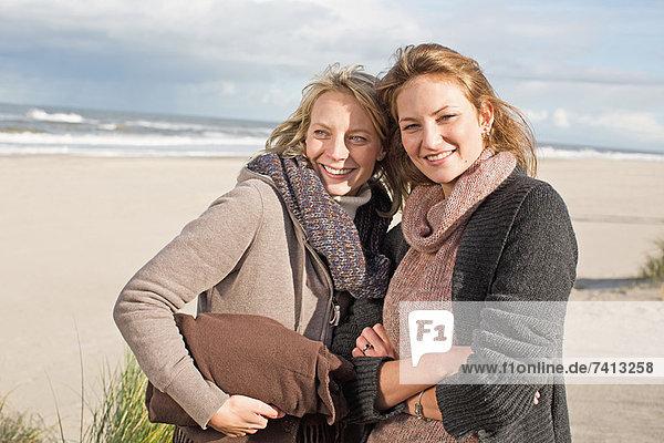Lächelnde Frauen stehen am Strand