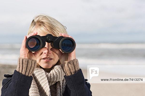 Frau mit Fernglas am Strand