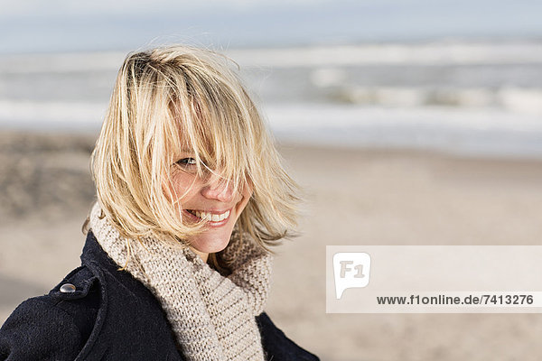 Lächelnde Frau am Strand stehend
