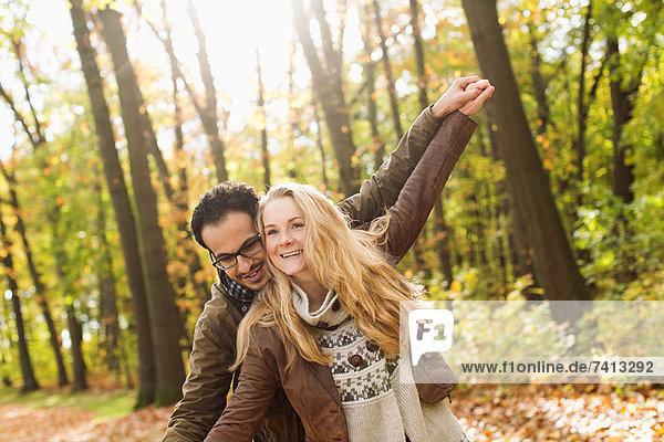 Lächelndes Paar umarmt sich im Wald Lächelndes Paar umarmt sich im Wald