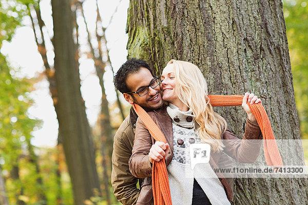 Lächelndes Paar umarmt sich im Wald