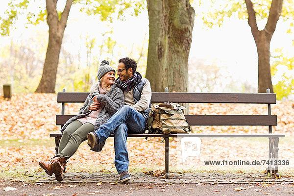 Lächelndes Paar auf der Parkbank sitzend
