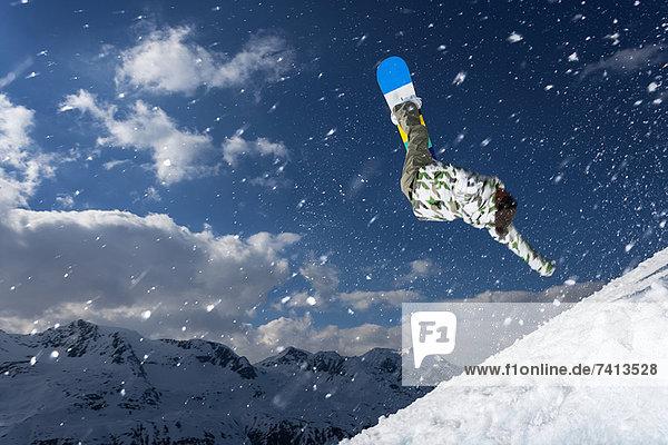 Snowboarder springen auf verschneiter Piste