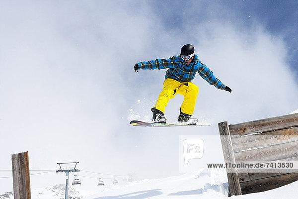 Snowboarder beim Springen vom Holzzaun