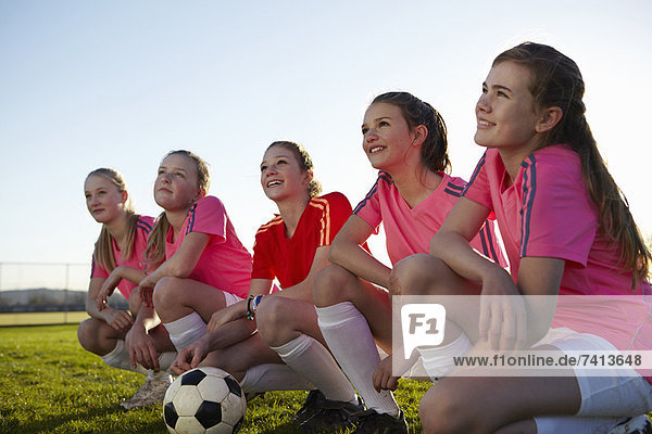 Football team smiling together in field