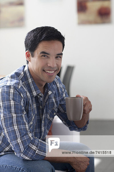 Portrait of man drinking coffee in living room
