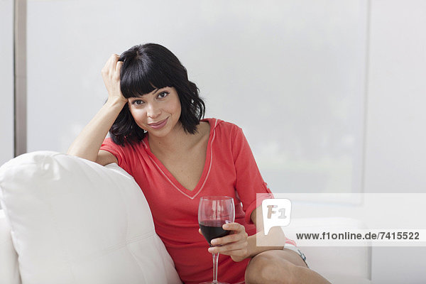 Young woman sitting on sofa with glass of wine