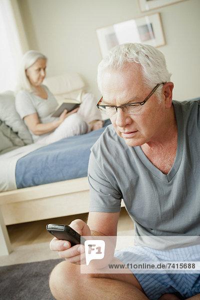 Handy  Senior  Senioren  benutzen  Frau  Mann  Buch  Bett  Kurznachricht  Taschenbuch  vorlesen