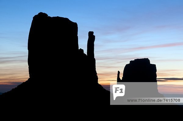 The famous Mittens are silhouetted at sunrise in Monument Valley  AZ.