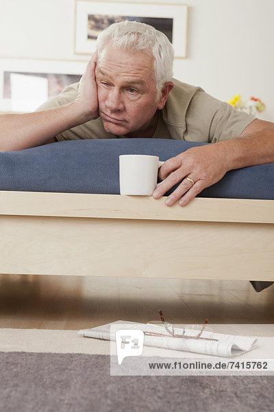 liegend liegen liegt liegendes liegender liegende daliegen Senior Senioren Mann Tasse halten müde Bett Kaffee