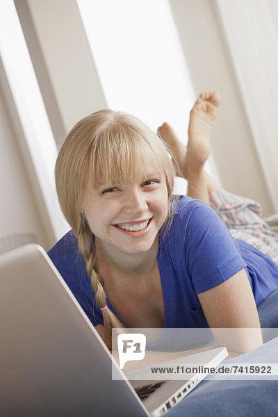 liegend  liegen  liegt  liegendes  liegender  liegende  daliegen  benutzen  Portrait  Frau  Notebook  lächeln  Bett  jung