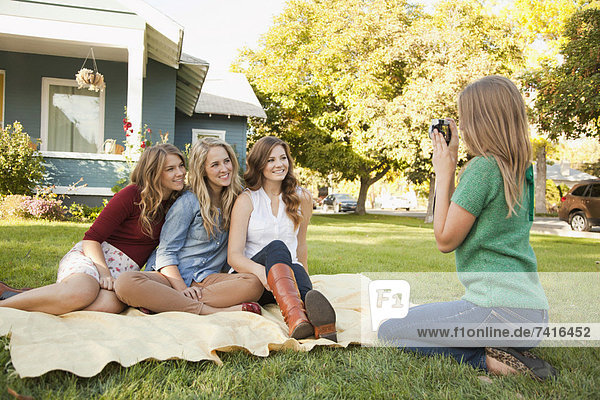 Young woman taking picture of her friends