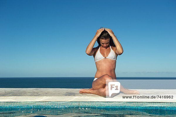 Pretty young woman relaxing in a swimming pool with sea view.