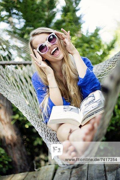 Farbaufnahme Farbe sitzend junge Frau junge Frauen lachen Buch Hängematte Kleidung Taschenbuch vorlesen