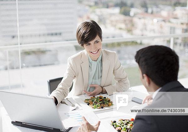Geschäftsmann und Geschäftsfrau mit Laptop-Meeting beim Mittagessen