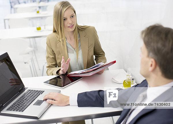 Geschäftsmann und Geschäftsfrau diskutieren über Papierkram