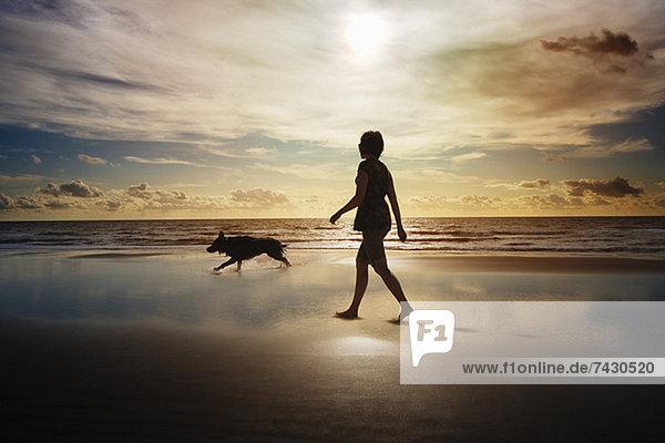 Silhouette von Frau und Hund beim Spaziergang am Strand