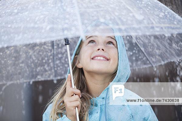 Nahaufnahme des lächelnden Mädchens unter dem Schirm im Regenschauer