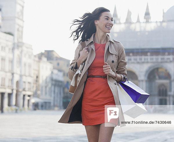 Lächelnde Frau mit Einkaufstaschen auf dem Markusplatz in Venedig