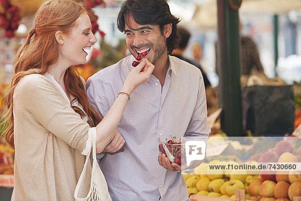 Lächelndes Paar schmeckt Obst auf dem Markt
