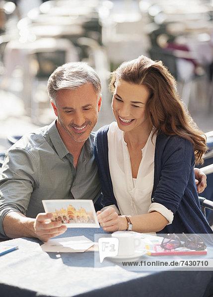 Lächelndes Paar schaut auf Postkarte im Straßencafé