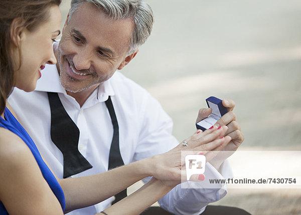 Mann mit Verlobungsring  der der Frau einen Antrag macht.