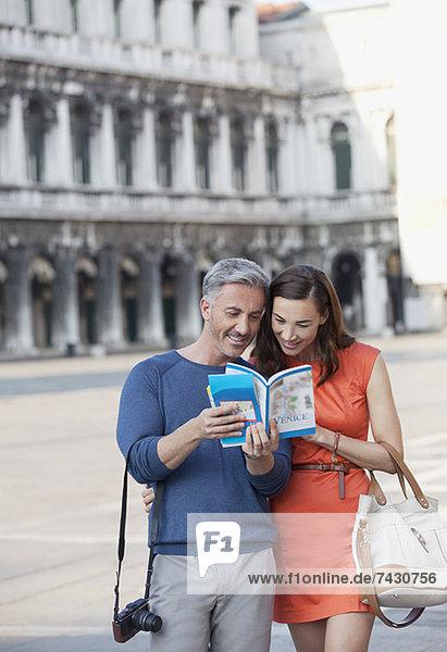 Lächelndes Paar schaut sich den Reiseführer auf dem Markusplatz in Venedig an.