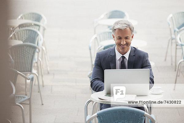Lächelnder Geschäftsmann mit Laptop im Straßencafé